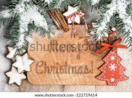 """Christmas greeting card: burnt words """"Merry Christmas"""" on wooden board decorated with Xmas tree twigs, snow, toys and sweet Xmas cookies - stock photo"""