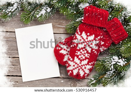 Christmas greeting card, fir tree and mittens on wooden table. Top view with copy space