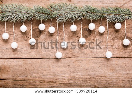 christmas greeting card, hanging white ball on wooden background - stock photo