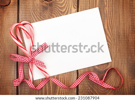 Christmas greeting card or photo frame over wooden table with candy canes. View from above - stock photo