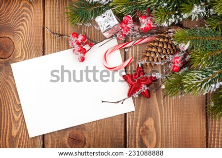 Christmas greeting card or photo frame over wooden table with snow fir tree. View from above - stock photo