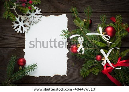 Christmas greeting card over old wooden table with decorations. View from above