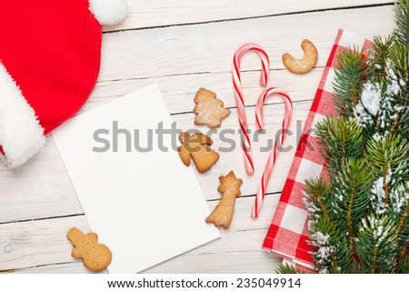 Christmas greeting card, santa hat, gingerbread cookies and snow fir tree. View from above over white wooden table background - stock photo