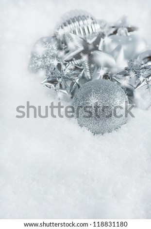 Christmas greeting card. Silver Christmas decorations in snow with sparkles, copy space, vertical