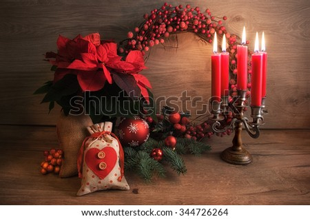 Christmas greeting card with candles and decorated Christmas tree on wooden table. This image is toned. - stock photo