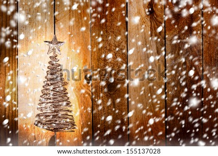 Christmas greeting card with gold metal firtree on the wooden snowy background - stock photo