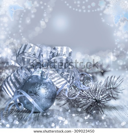 Christmas greeting card with toys and decorations in silver and blue, space for your text. Shallow DOF, focus on the stripy bow. - stock photo