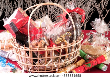 Christmas hamper basket with a chocolate Santa, cookies and a bottle of wine  - stock photo