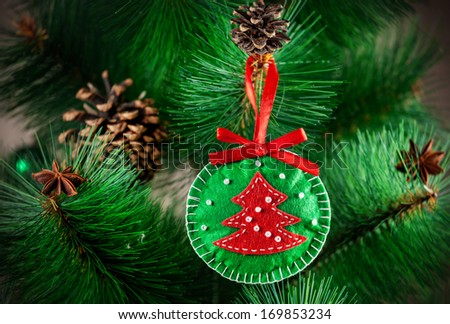Christmas handmade green toy from felt on the Christmas tree with cones - stock photo
