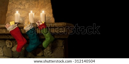 Christmas hanging stockings on fireplace background. Chimney, candles. Christmas socks, decoration, gifts. Copy space, black background - stock photo