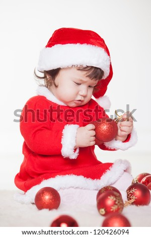 Christmas happy baby in Santa hat playing with balls. Isolated on white background.