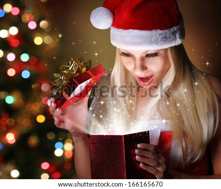 Christmas. Happy Blonde Girl with Santa Hat Opening Gift Box over lights of Christmas tree. Miracle  - stock photo