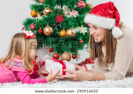 Christmas Happy Family mother and her little daughter open Holidays Gift. - stock photo