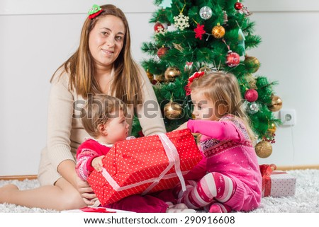 Christmas Happy Family mother and her two little daughters sitting on the floor and open Holidays Gift.