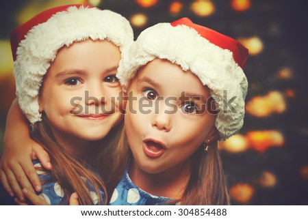 Christmas Happy funny children twins sisters hugging  - stock photo