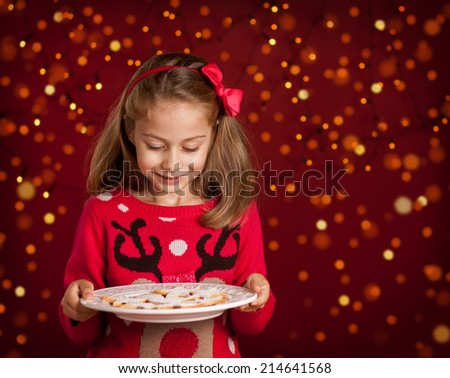 Christmas - happy smiling six years old blond caucasian child girl holding cookies plate on dark red background with lights - stock photo