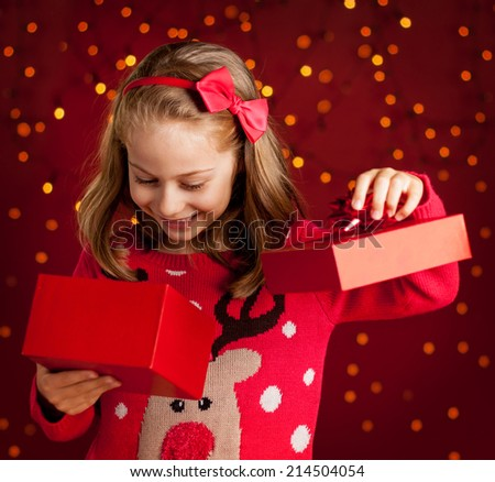 Christmas - happy smiling six years old blond caucasian child girl opens present on dark red background with lights - stock photo