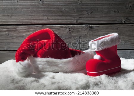 Christmas hat and boot on heap of snow against wooden background - stock photo
