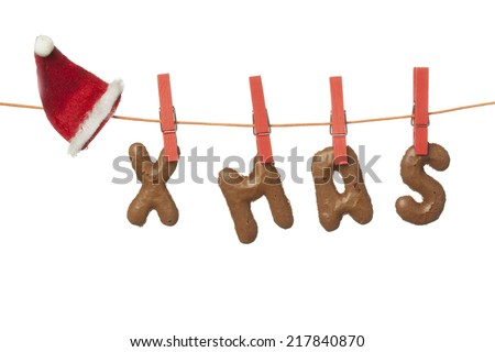 Christmas hat and Xmas letters hanging on washing line, isolated on white background - stock photo