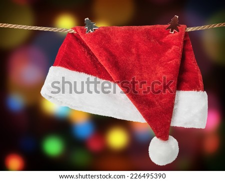 Christmas Hat Santa claus hanging on a rope with clothespins - stock photo