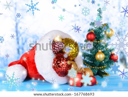Christmas hat with Christmas decorations on table on light background