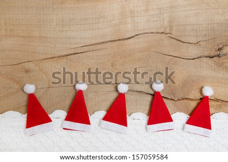 Christmas hats, crocheted snow on wooden background - stock photo