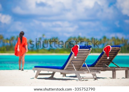 Christmas hats on beach loungers at white beach in Maldives - stock photo