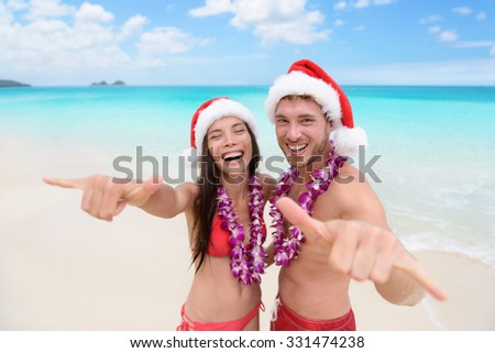 Christmas Hawaii vacation - Hawaiian beach couple wearing santa hat and doing welcome shaka sign happy at camera as welcoming gesture for winter holidays. - stock photo