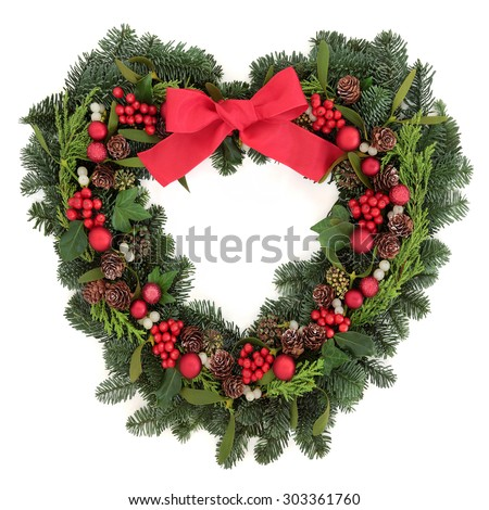 Christmas heart shaped wreath with red bauble decorations and bow, holly, mistletoe, ivy and winter greenery over white background. - stock photo