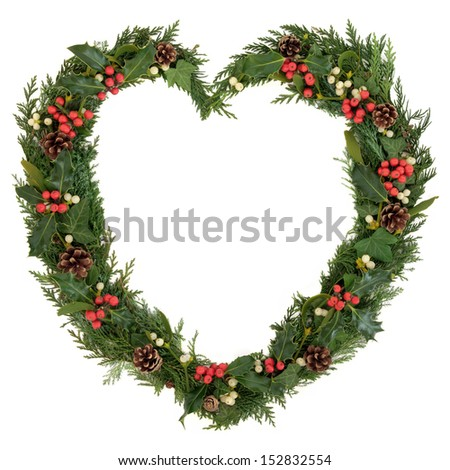 Christmas heart wreath with holly, mistletoe, ivy, pine cones and cedar leaf sprigs over white background. - stock photo