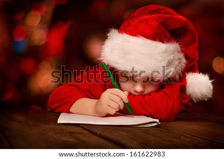 Christmas helper child writing letter to Santa Claus letter in red hat