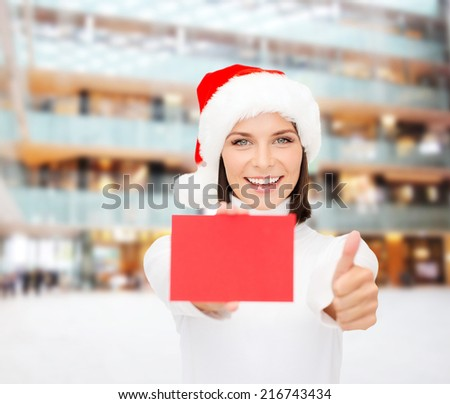 christmas, holdays, people, advertisement and sale concept - happy woman in santa helper hat with blank red card showing thumbs up gesture over shopping center background - stock photo