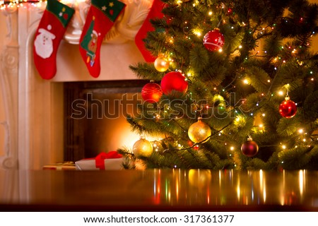 Christmas holiday background of wooden table against decorated Christmas tree and fireplace