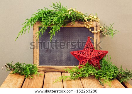 Christmas holiday background with chalkboard, ornaments and pine tree branches - stock photo