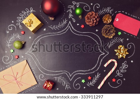 Christmas holiday background with decorations and hand drawings on chalkboard. View from above