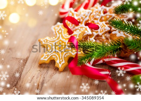 Christmas Holiday background with Gingerbread Cookies, Candy Cane and evergreens border over wooden table. Christmas and New Year food backdrop