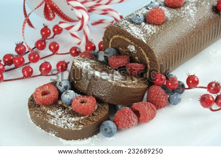 Christmas holiday chocolate roulade yule log swiss roll with berries dessert party food - closeup. - stock photo