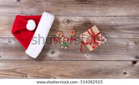 Christmas holiday cookies, gift and Santa cap on rustic wood.
