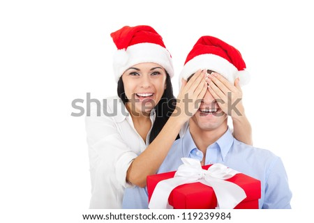 christmas holiday couple happy young female surprise husband cover his eyes, pretty woman covering mans eyes, excited smile, isolated over white background - stock photo
