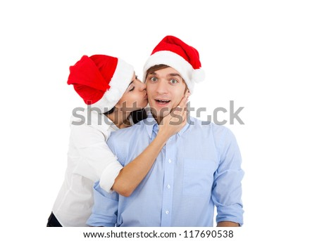 christmas holiday couple kiss love embracing in red new year hat cap, isolated over white background - stock photo