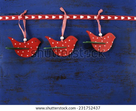 Christmas holiday festive natural style wood red polka dot bird ornaments on a dark royal blue vintage recycled wood background.