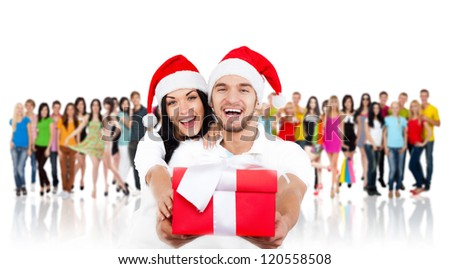 christmas holiday happy couple hold present gift box wear red new year santa hat cap, man and woman love smile over big group of casual people diverse student background - stock photo