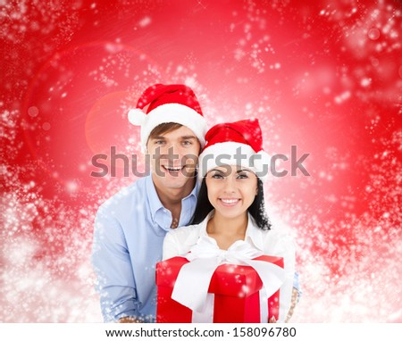 christmas holiday happy couple hold present gift box wear red new year santa hat cap, man and woman embracing, over abstract magic winter background with sparkles blowing snow
