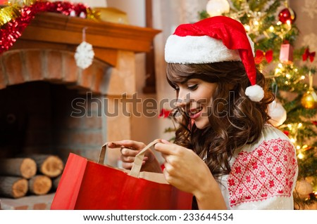 Christmas holiday happy girl after shopping exploring bags, in christmas decorated living room ,wear red new year santa hat, over chimney and christmas tree colorful lights background - stock photo