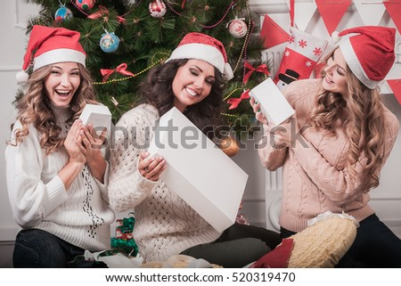 Christmas holiday happy girl friends exchanging presents in christmas decorated living room, wear red new year santa hat. Holding white box with copy space for you text or logo