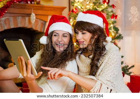 Christmas holiday happy girl friends looking at something on digital touch screen tablet PC, wearing red new year santa hat, over chimney and christmas tree colorful lights background.  - stock photo