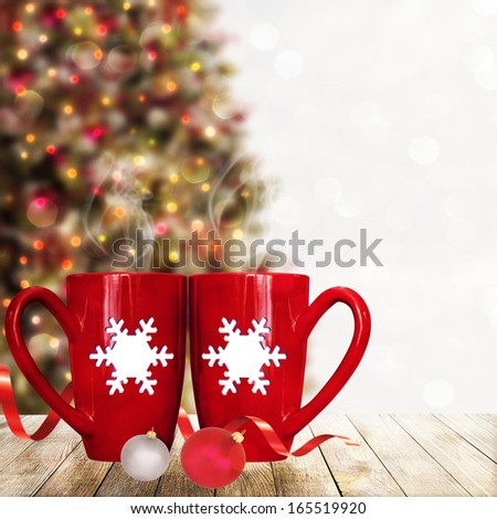 Christmas holiday mugs on wooden  terrace over Christmas tree bokeh background - stock photo