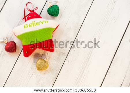 "Christmas holiday ornaments soft felt star with ""believe"" writing and glittery hearts on wooden rustic background with free space - stock photo"