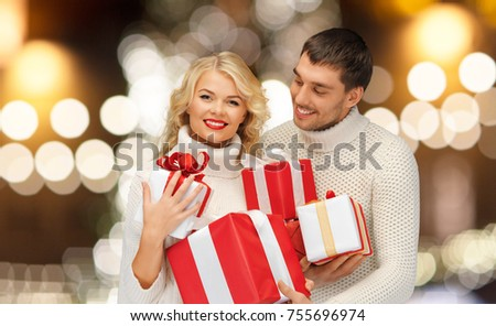 christmas, holidays and new year concept - happy family couple in sweaters holding gifts or presents over lights background