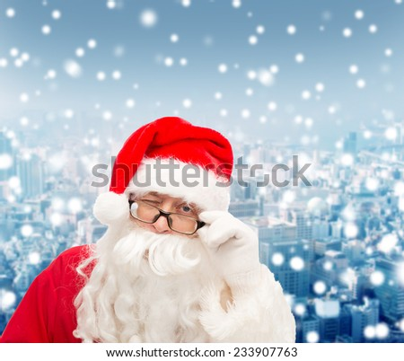 christmas, holidays and people concept - close up of santa claus in glasses winking over snowy city background